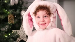 Happy little girl in pink bunny costume near christmas tree Stock Footage