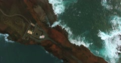 AERIAL: birds's-eye view of a lighthouse on a cliff with green ocean waves - stock footage