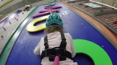 Girl climbs on letters in attraction Big Wall KIDS in Climbing Center Stock Footage