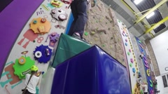 Girl climbs on cubes in attraction Big Wall KIDS in Climbing Center Stock Footage