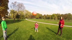 Happy mother, son, daughter play ball in fall park, camera on head Stock Footage