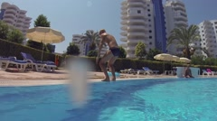 Teen boy does somersault and jumps into pool outdoor Stock Footage