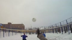 Two pairs of men playing volleyball in snow on winter day Stock Footage