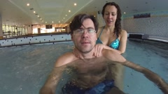 Young woman in blue bikini massages man, man makes selfie in pool Stock Footage