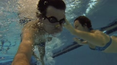 Man in goggles swims with woman in indoor pool and makes selfie Stock Footage