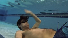 Man in goggles swims close to bottom in pool and makes selfie Stock Footage