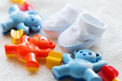 Close up of baby rattle and bootees for newborn Stock Photos