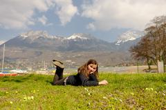 pretty preteen is lying in the green grass - stock photo