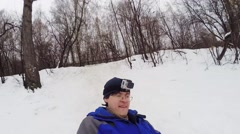 Man with camera on head down hill on snowtube and makes selfie Stock Footage