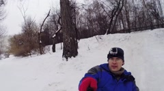 Man with camera on head down hill on snowtube, makes selfie Stock Footage