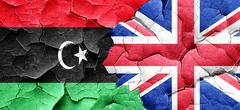 Libya flag with Great Britain flag on a grunge cracked wall Stock Illustration