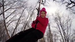 Happy girl rides bungee in winter snowy forest, under view Stock Footage