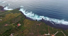 AERIAL: tilt shot of ocean and green coast Stock Footage