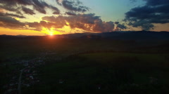 Green hills and country village at sunset, camera rise - stock footage