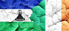 Lesotho flag with Ireland flag on a grunge cracked wall - stock illustration