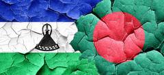 Lesotho flag with Bangladesh flag on a grunge cracked wall - stock illustration