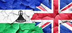 Lesotho flag with Great Britain flag on a grunge cracked wall Stock Illustration