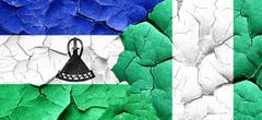 Lesotho flag with Nigeria flag on a grunge cracked wall Piirros