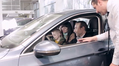 Sales manager advises family in choosing a new car - stock footage