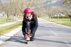 Pretty preteen girl on roller skates in helmet Stock Photos