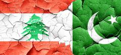 Lebanon flag with Pakistan flag on a grunge cracked wall - stock illustration