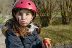 preteen with roller skate helmet, eat an apple - stock photo