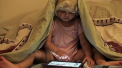 Little girl using tablet at bedtime. - stock footage