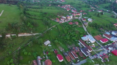 Flight over green hills and country village - stock footage