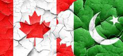 Canada flag with Pakistan flag on a grunge cracked wall - stock illustration