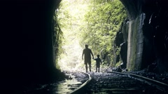 Father and son leaving the tunnel dark Stock Footage