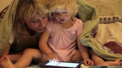 Little girl and mother playing on the computer tablet before bedtime. - stock footage