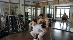 Trainer helps the beginner to do squats with barbell Stock Footage