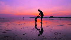 Father whirling his son on the beach - stock footage
