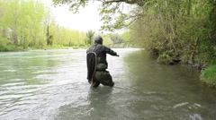 Fly-fisherman trying to take fish out Stock Footage