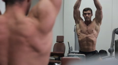 Man bodybuilder in front of the mirror getting ready for a competition Stock Footage