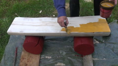 Farmer worker painting handmade  wooden bench with yellow paint Stock Footage