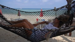 Woman Lying in Hammock on Beach against Sea Stock Footage