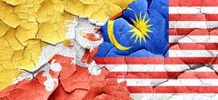 Bhutan flag with Malaysia flag on a grunge cracked wall Stock Illustration