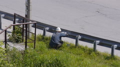 Worker is painting fences along the roadside Stock Footage
