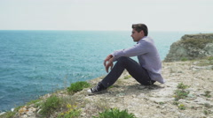 A young man sits on a rock and looking at the beautiful sea surf. Stock Footage