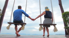 Young couple sitting on a swing admiring nature Stock Footage