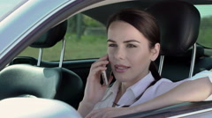 Young business woman in her car holding disposable coffee cup taking phone call - stock footage