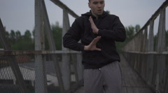 Active young male dancing on the bridge, blurred trees and sky behind him. Stock Footage