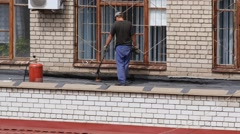 Young caucasian man repairing leaking roof layer Stock Footage