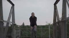 Active young male dancing on the bridge, trees and sky behind him. Stock Footage