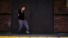 Active young male dancing on a black metal door and brick wall background. - stock footage