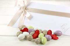 Colored sugared almonds and wedding paper Stock Photos