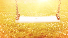 Empty swing in front of sunlight in slow motion Stock Footage