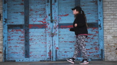 Young female dancing on an blue door and brick wall background in slow motion. Stock Footage