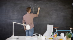 4K Man drawing light bulb on blackboard, education or creative office concept Stock Footage